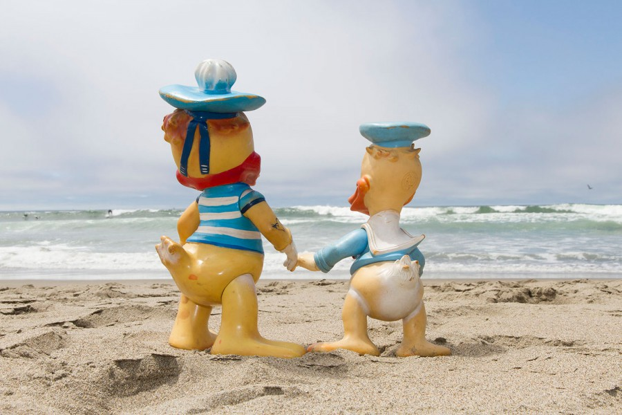 Donald Duck made by Disney and Donald Duck made in Romania holding hands looking at the horizon at Ocean Beach in San Francisco, California. If they went any further West, they would reach the East. They turn us their back so the viewer can identify with their perspective.