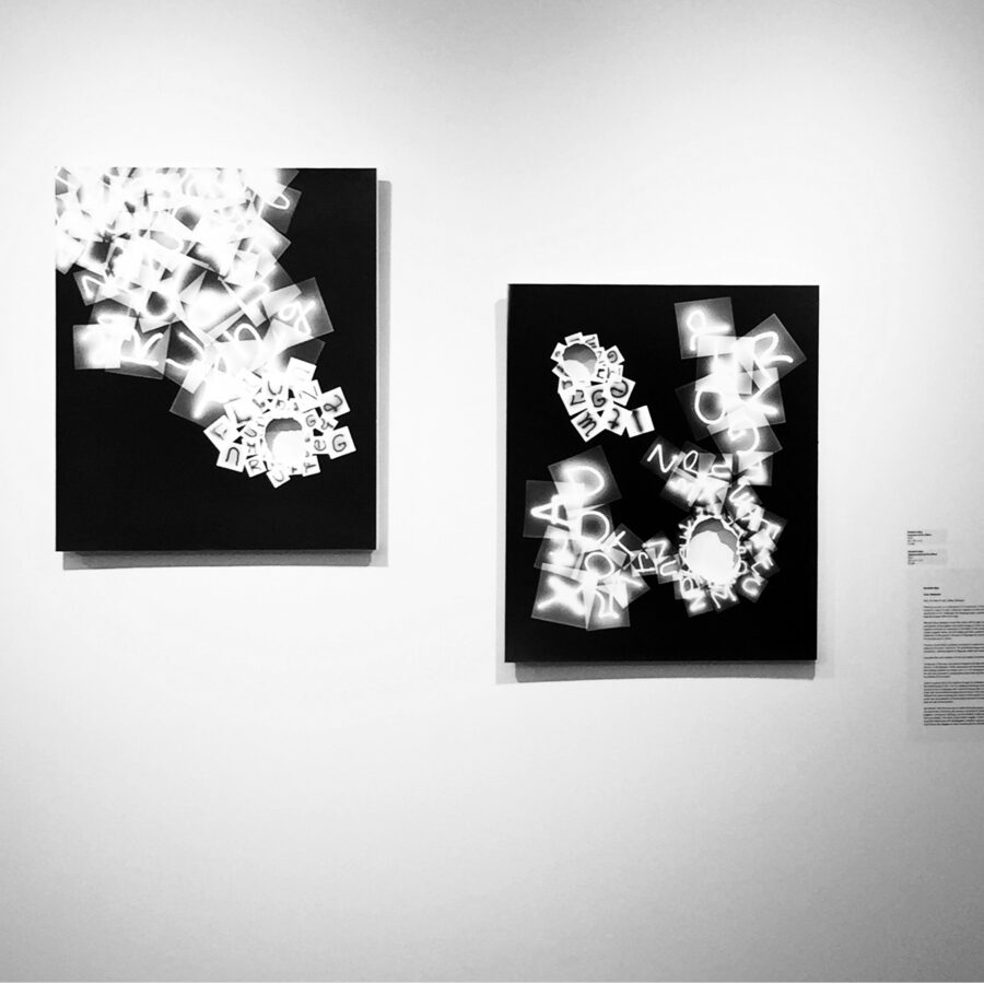 black and white photogram with white letters collapsing on a black surface