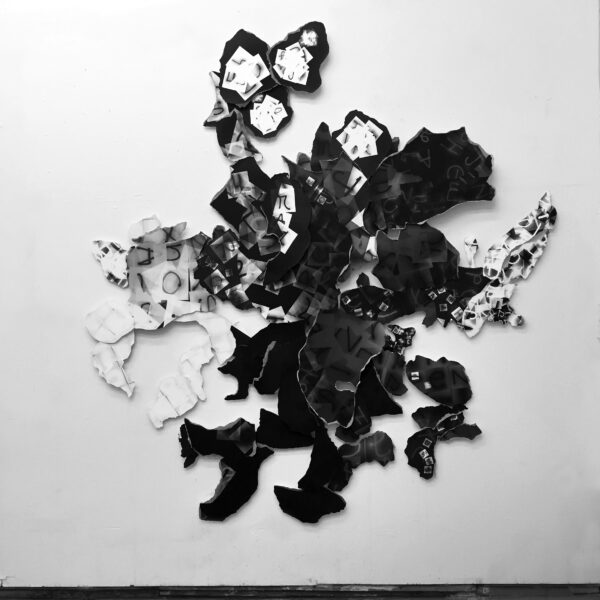 collaged photograms with letters overlaying each other in black and white torn pieces mounted on museum board are assembled like a cartography