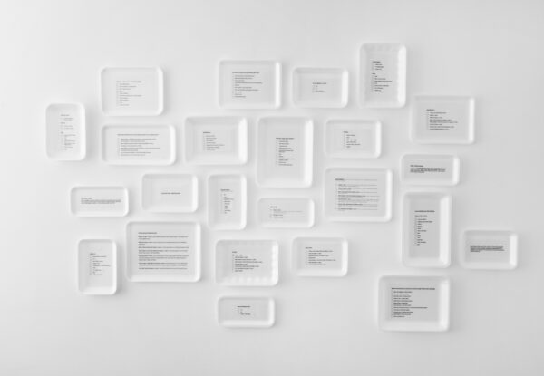 Installation view of white meat trays with print outs of diversity